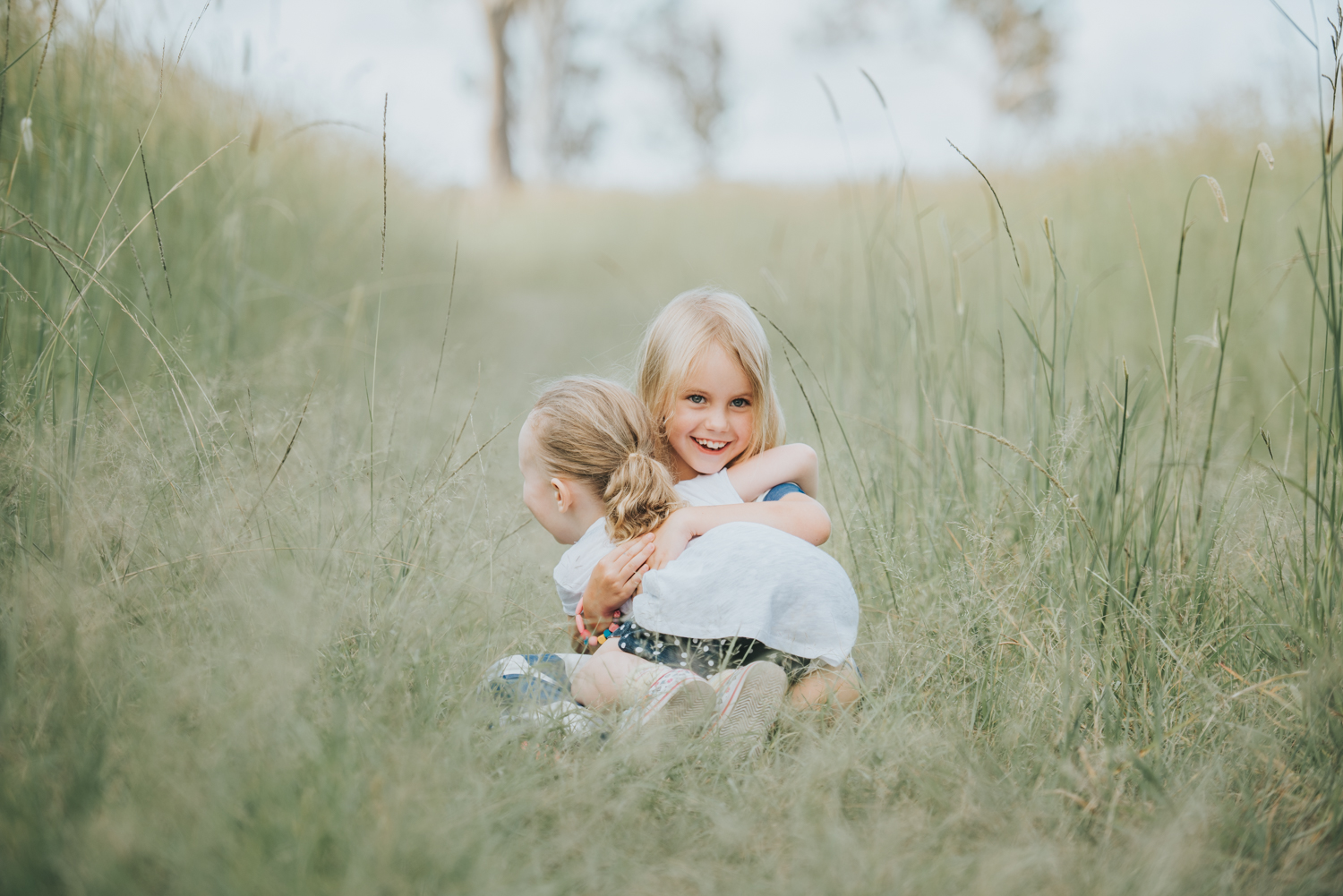 Sisters hugging in long grass | Sirromet Winery | Lightsmith Images