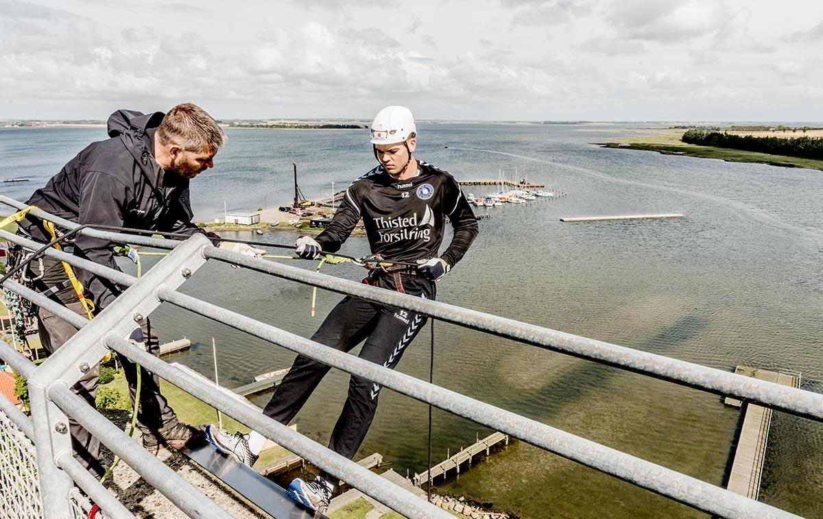Vores instruktør Thomas Kolding er ved at sende en ligaspiller fra Mors-Thy Håndbold ned ad tårnet på Doverodde Købmandsgård.