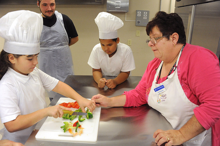 Lake Fong/Post-Gazette 09202016 Sonja Reis LocalFood instructor Cindy Stevans, (cq) right, teaches McKees Rocks residents from left, Dana Bruno, 10, Larry Rodgers, 25, and Kellen Kyles, 9, at Father Ryan Arts Center in McKees Rocks on Tuesday, September 20, 2016. The Family Table program teaches family oriented health, nutrition and cooking skills.