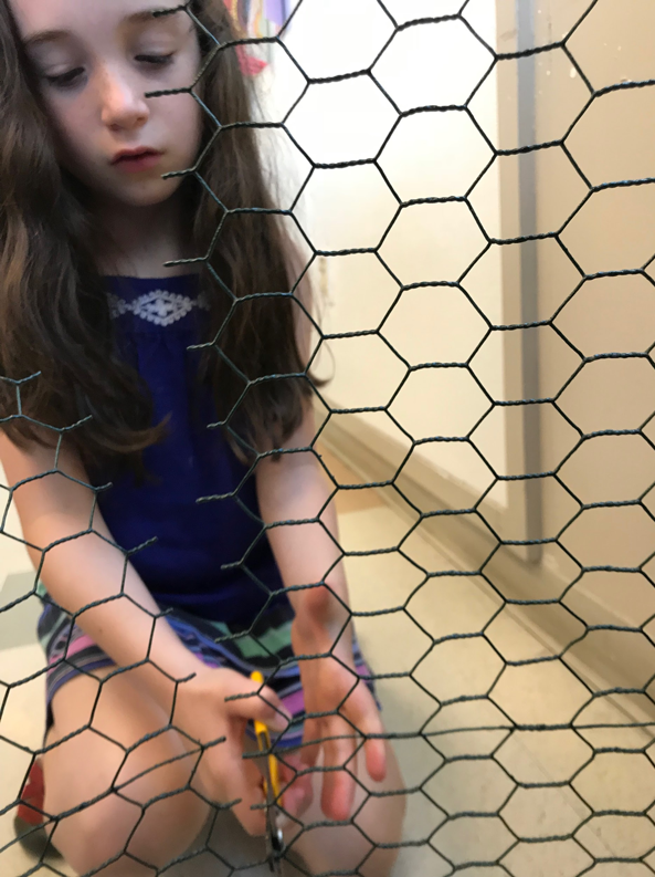 Student learns how to cut chicken wire for her Red Hawk sculpture