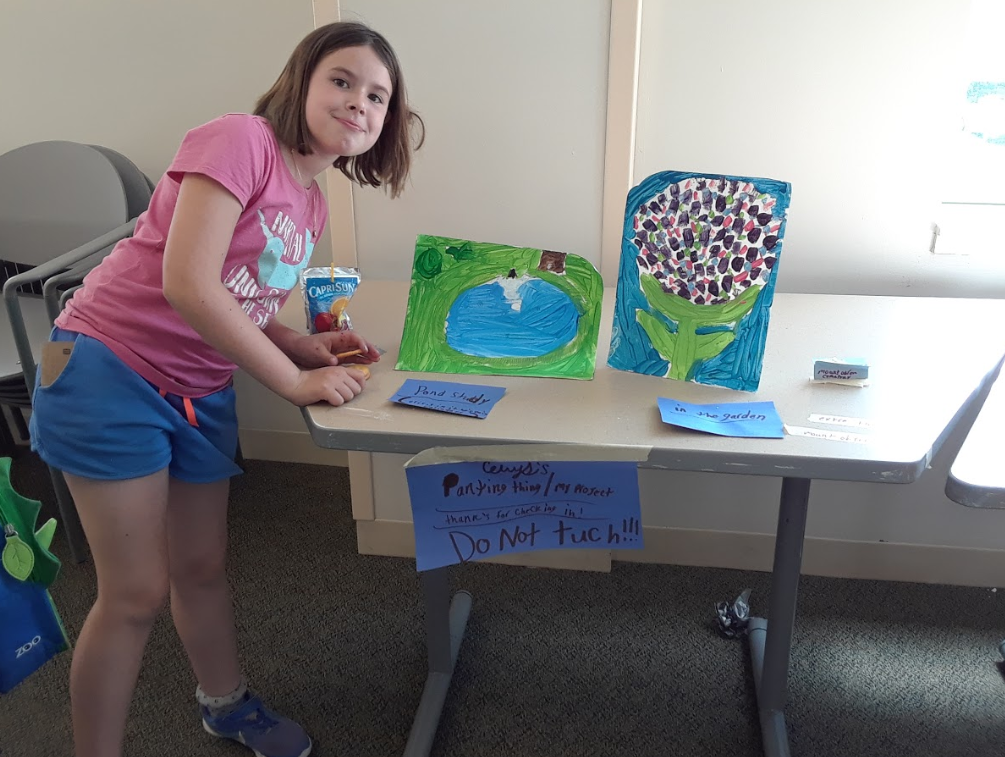 Student with her paintings of Consecration Dell and the garden