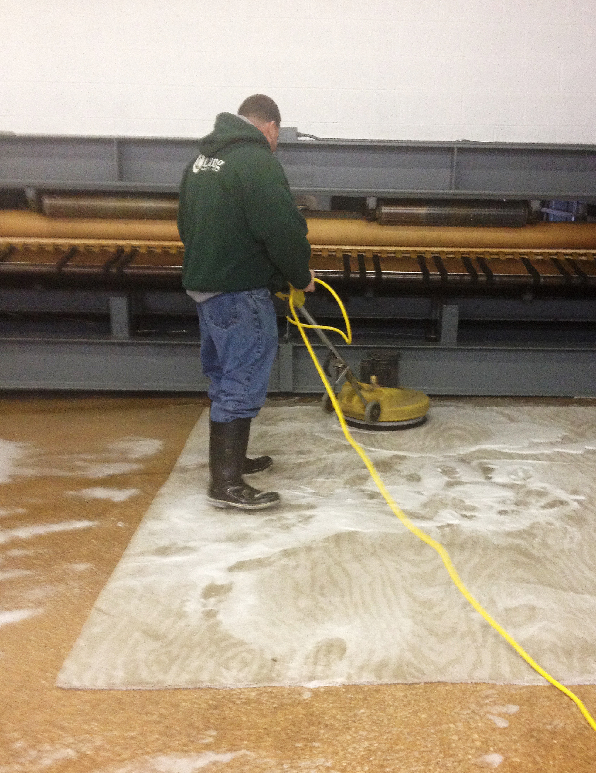 This is a picture of one of our team members cleaning an area rug in our in-house rug cleaning facility.