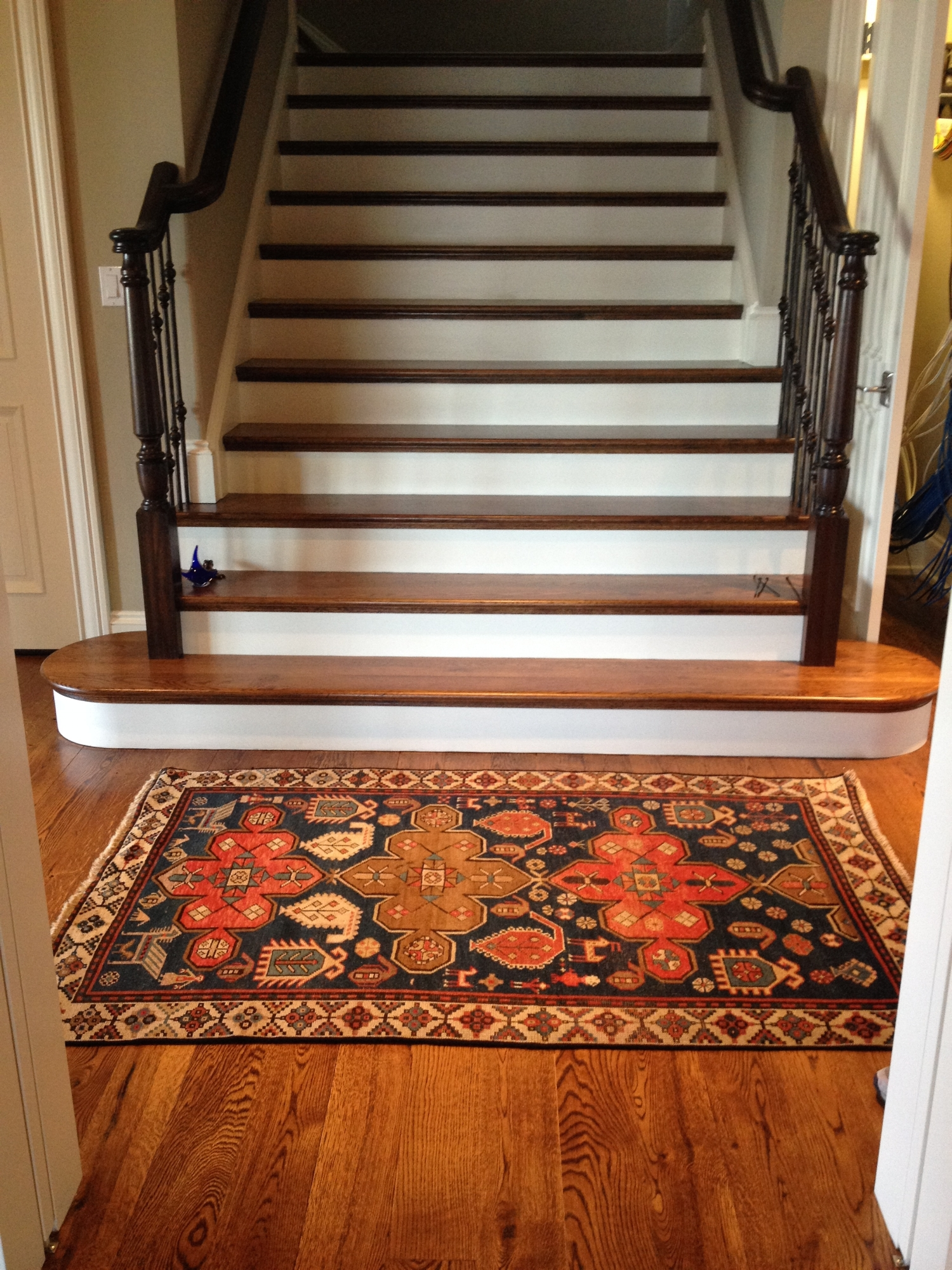Antique Persian rug at the bottom of a beautiful set of stairs