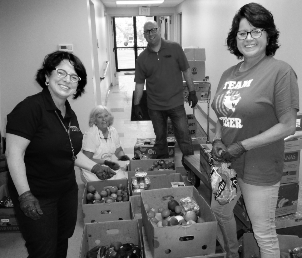Tiger Natural Gas team sorting produce for Grocery Pantry on the day they sponsored.
