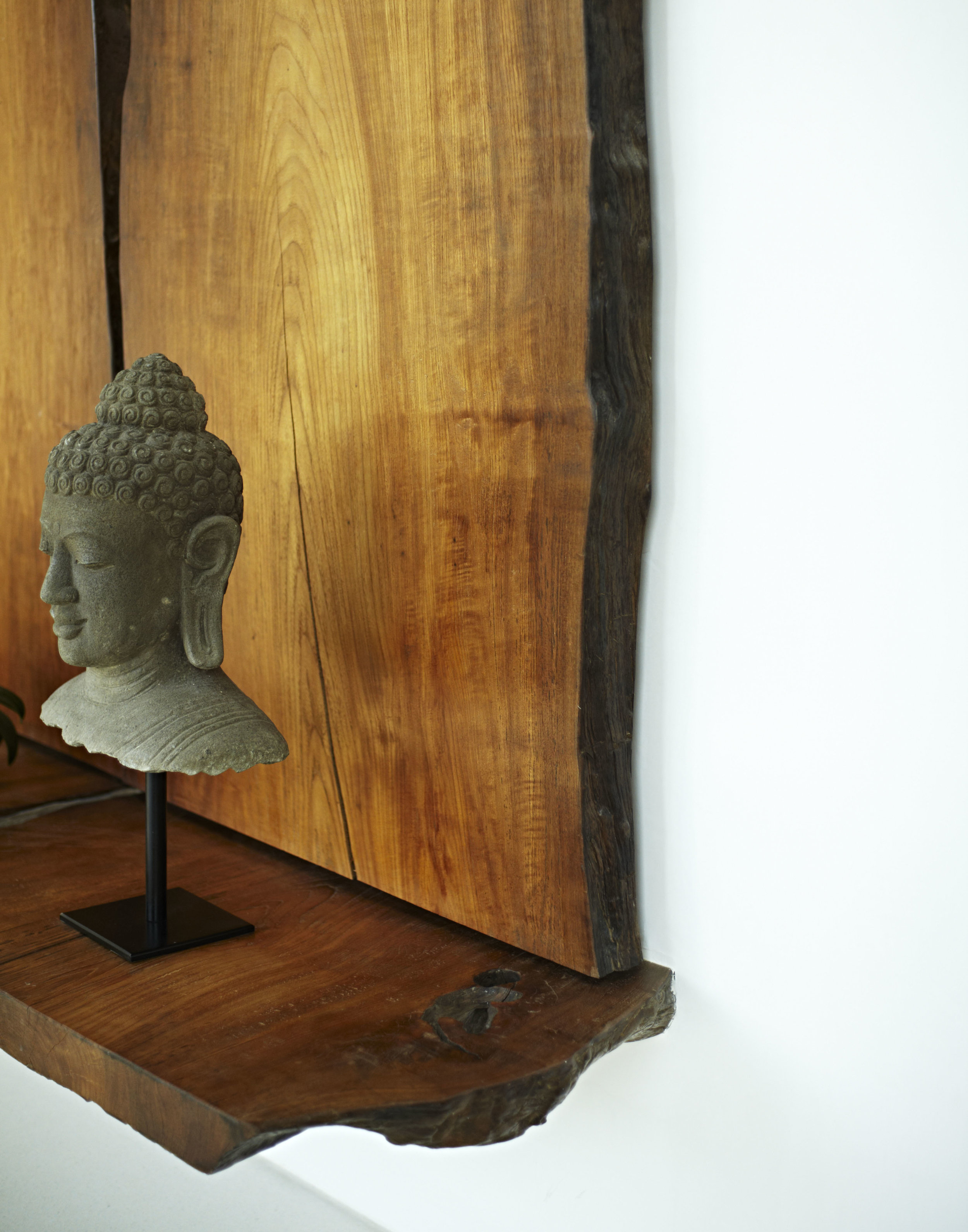 Buddha sculpture and wooden wall hanging and bench