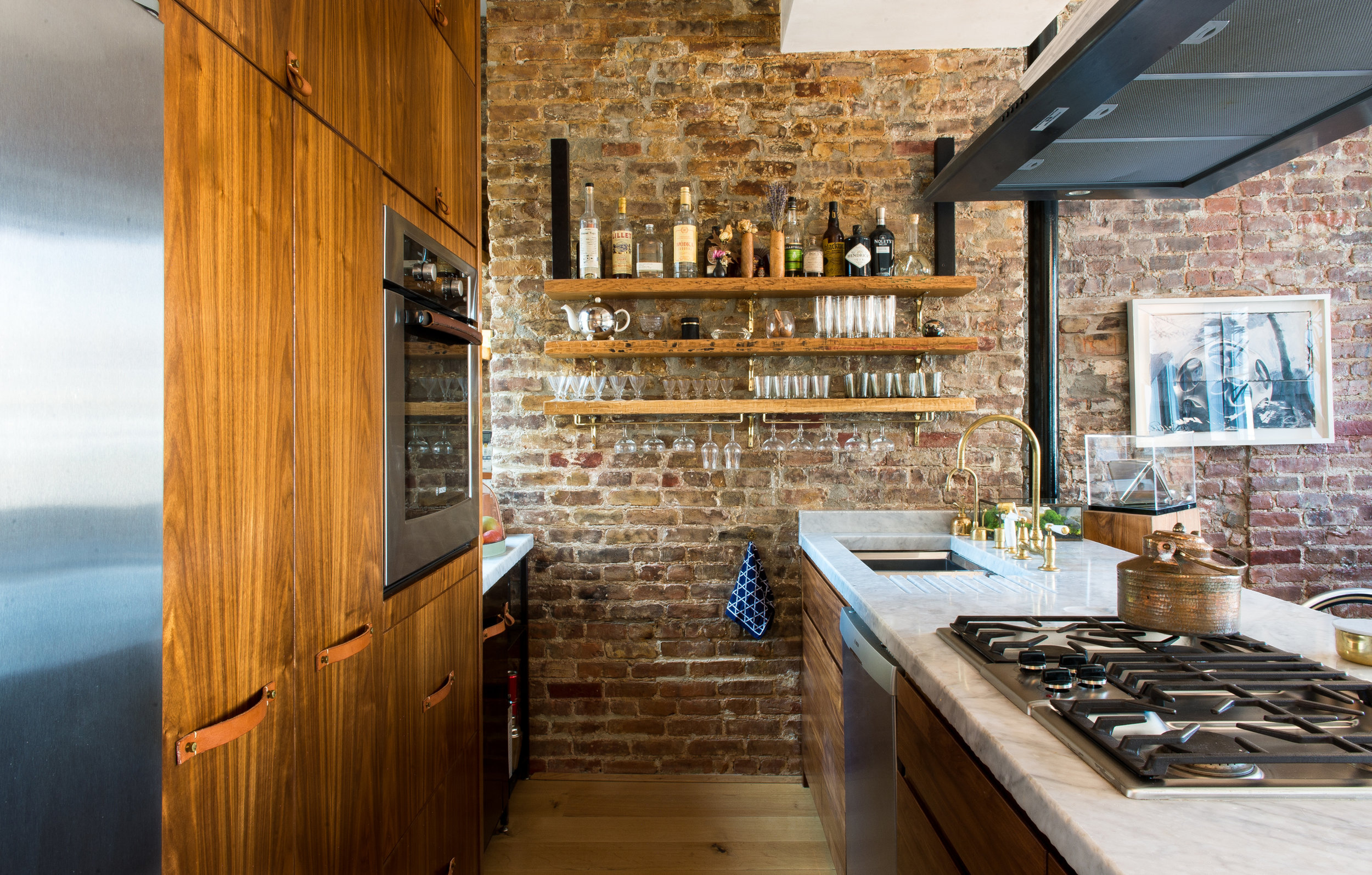 Modern New York apartment kitchen with open shelving, exposed brick, marble slabs and American walnut cabinetry