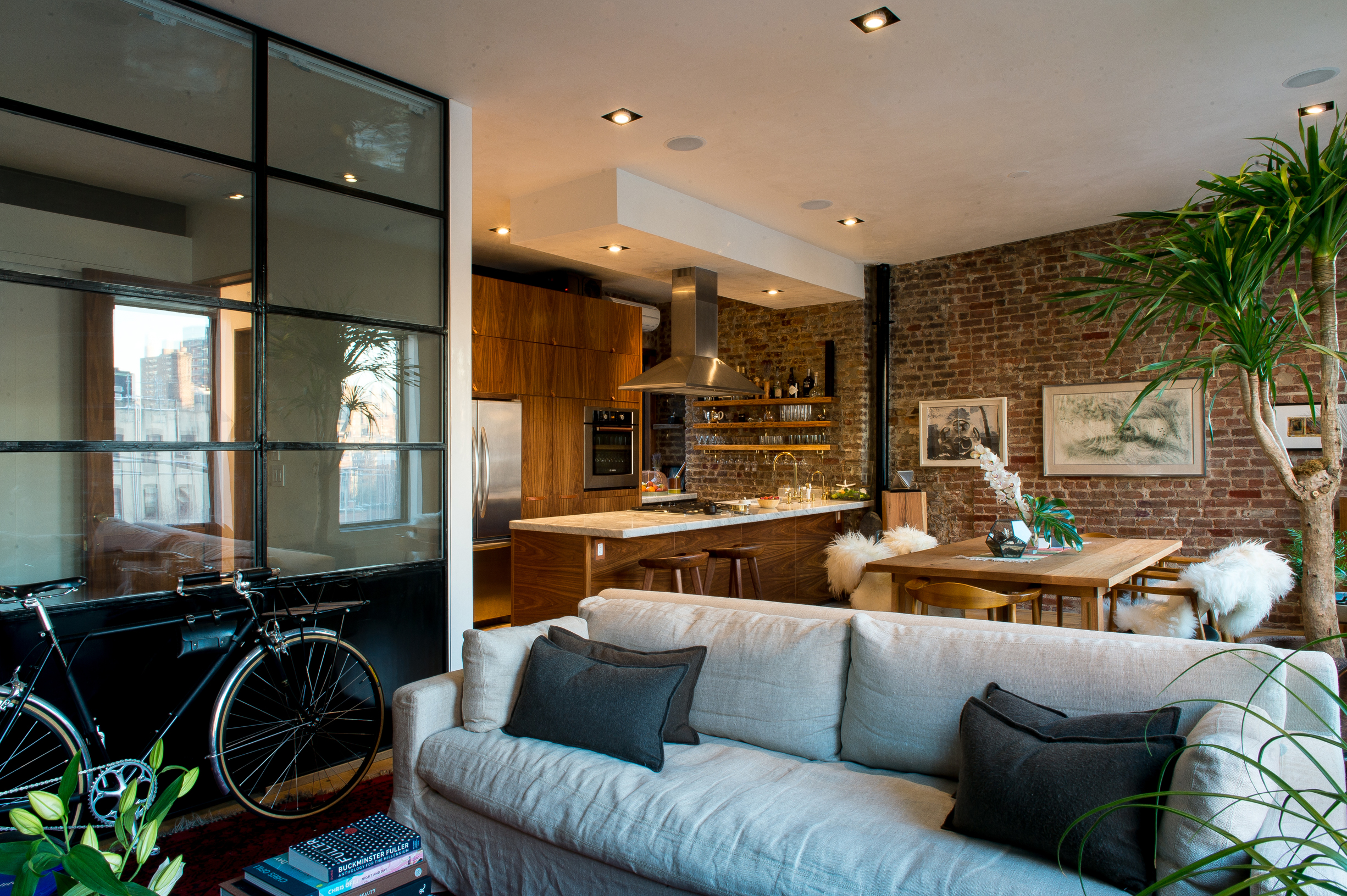 Modern New York loft apartment with couch, open kitchen, open shelving, American walnut cabinetry