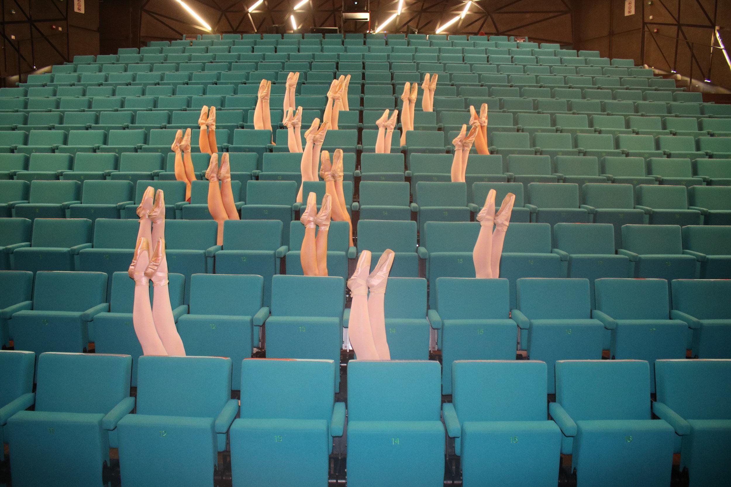 Demi-pointes en pointes - Aan de voeten draag je Footundeez (beschermers voor de blote voeten) of je werkt op blote voeten.In de pointesklassen dragen de leerlingen hun klasuniform met roze/vleeskleurige pointes. De vorm van de voet bepaalt het merk dat je draagt. Deze schoenen kopen de leerlingen zelf bij de gespecialiseerde handelaars.Ook jongens kunnen deelnemen aan de pointesklassen. Die dragen zwarte pointes.