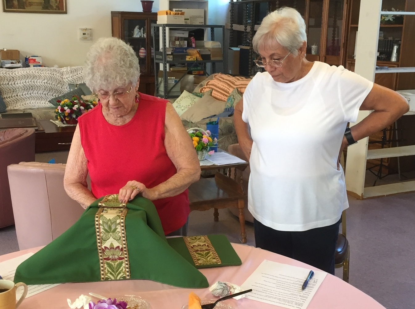"""Altar guild member shirley mosher practices setting """"the stack"""" that will be placed on the altar, under the watchful eye of Rose Applegate. The """"stack competition"""" was part of the recent St. James Altar Guild Games, designed to be a fun way to hone alter guild skill"""