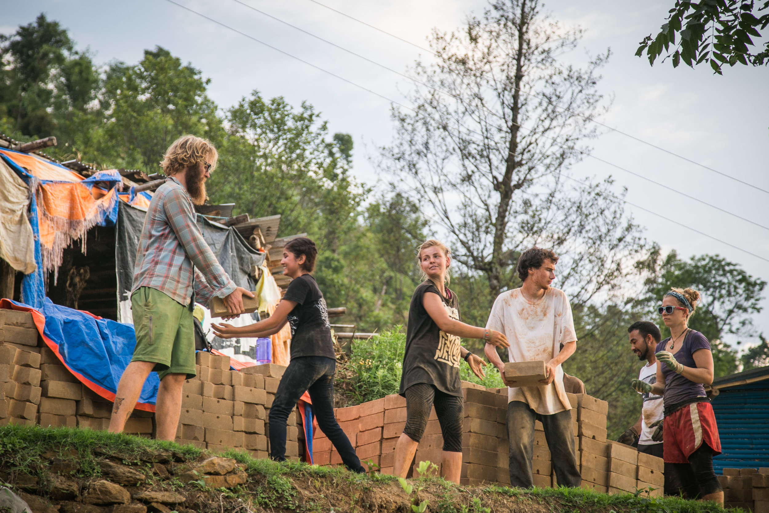 Volunteers moving earth blocks to the site.