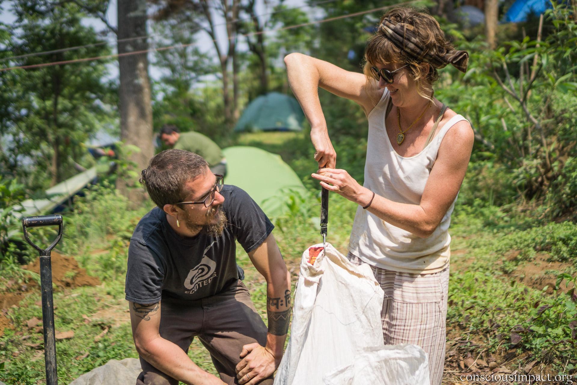 Volunteers Meryl and Jatesh measure 6 kg of humanure per tree!