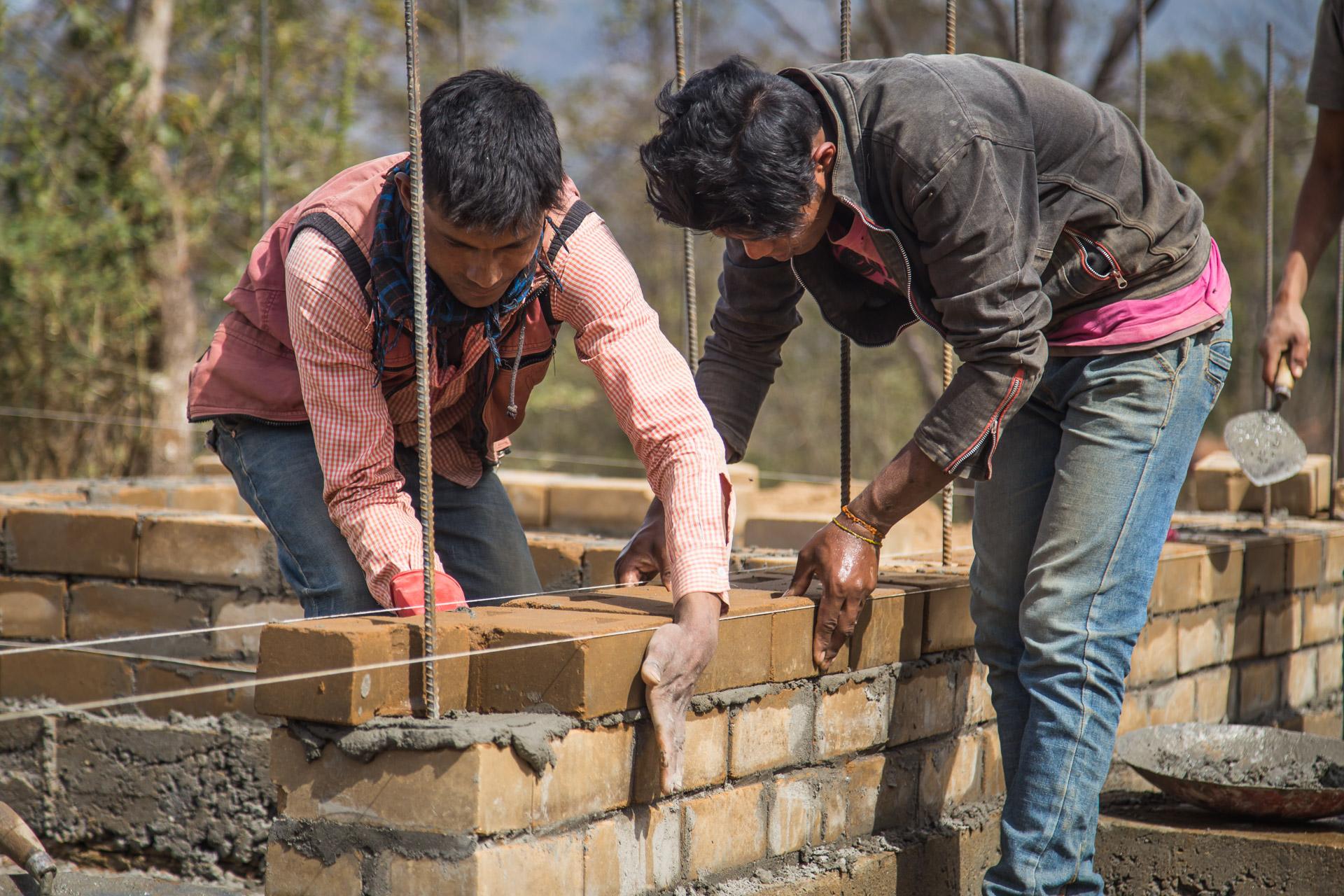 Masons laying bricks around rebar to ensure earthquake resistance.