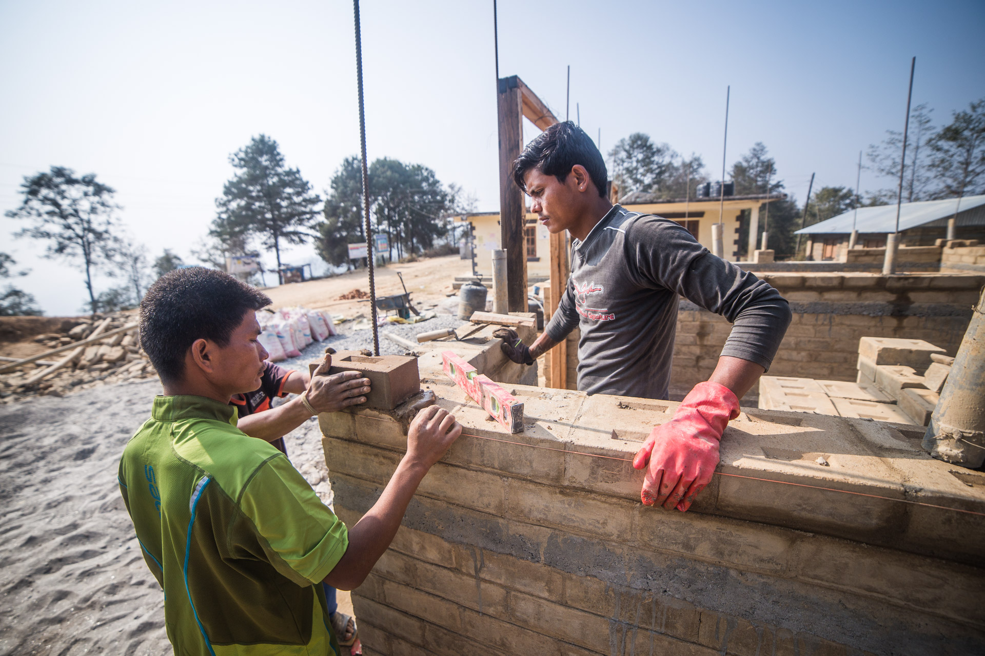 Our awesome team of masons laying earth blocks around rebar for earthquake resistance.