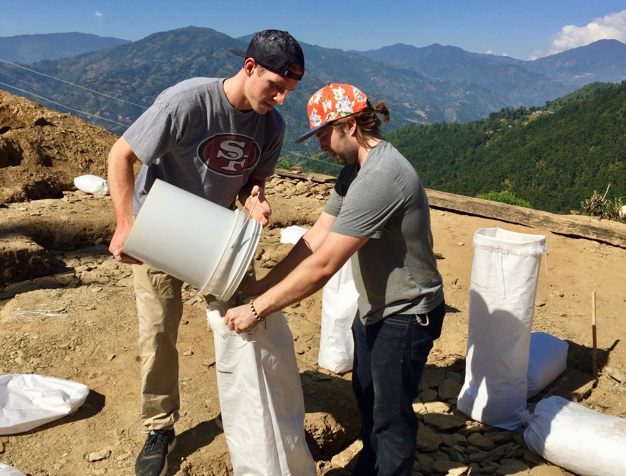 Alex and Mac, two volunteers, fill a bag with gravel as part of the foundation construction. The home sits on a bluff with a beautiful view of the Langtang mountain range.
