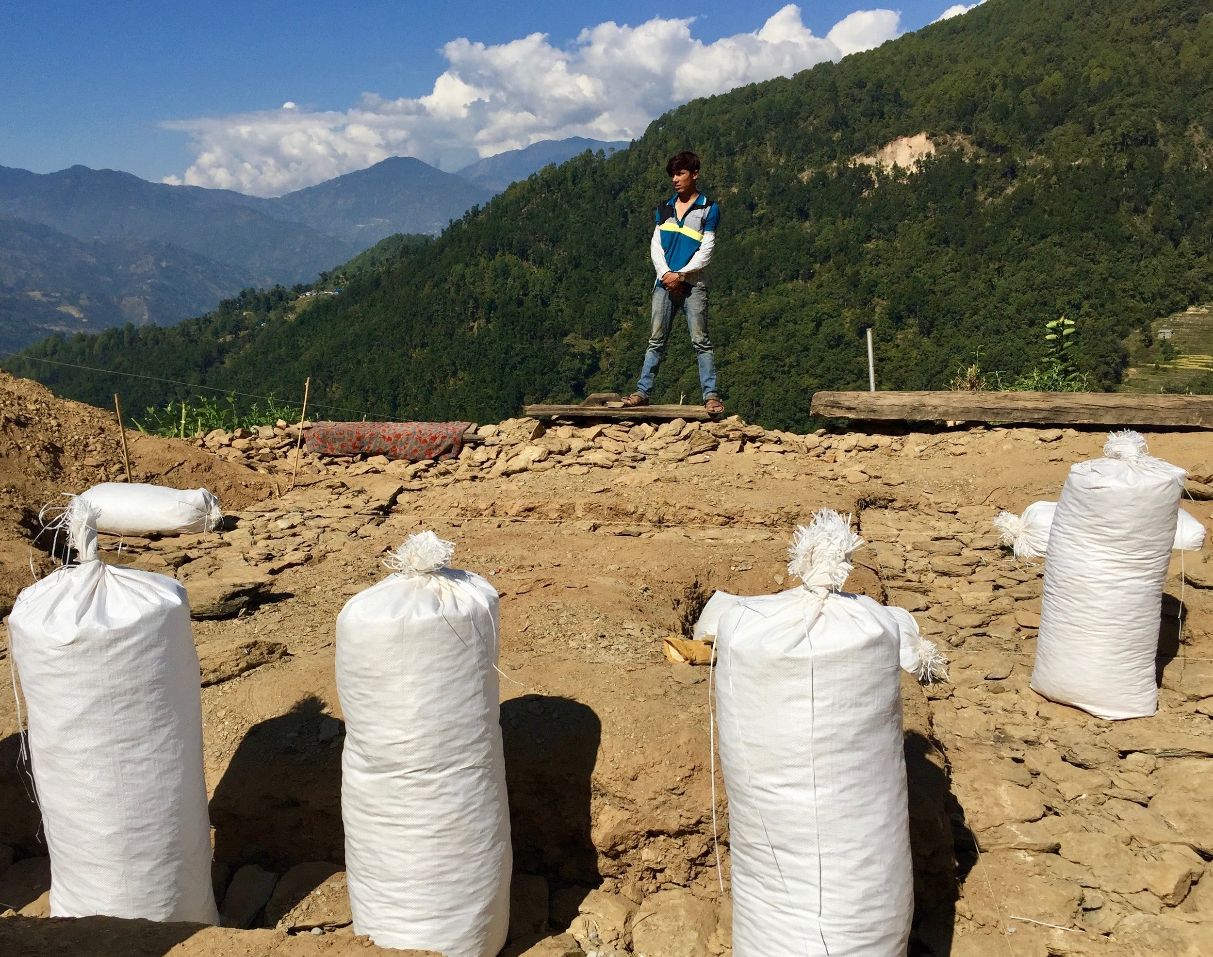 The family's son Namraj stands on the edge of the construction site at the end of a morning's work admiring the progress. Filled gravel bags cover the site and the Langtang mountain range hides behind the clouds in the distance.