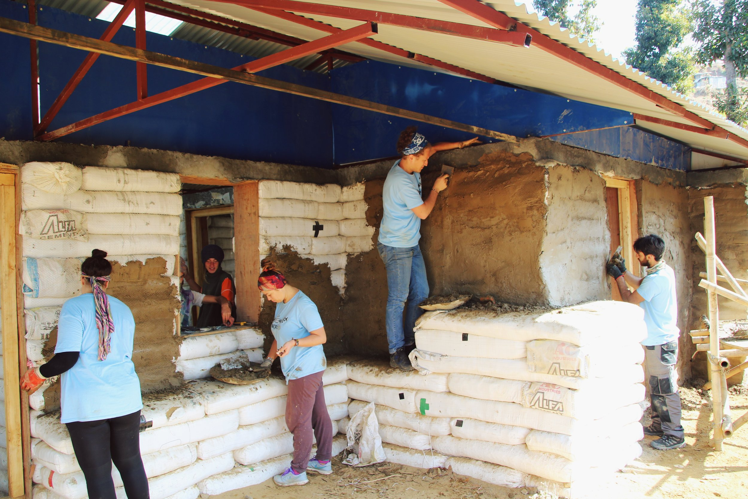 Plastering the Coffee Cooperative's outside walls in February. The project is now complete!