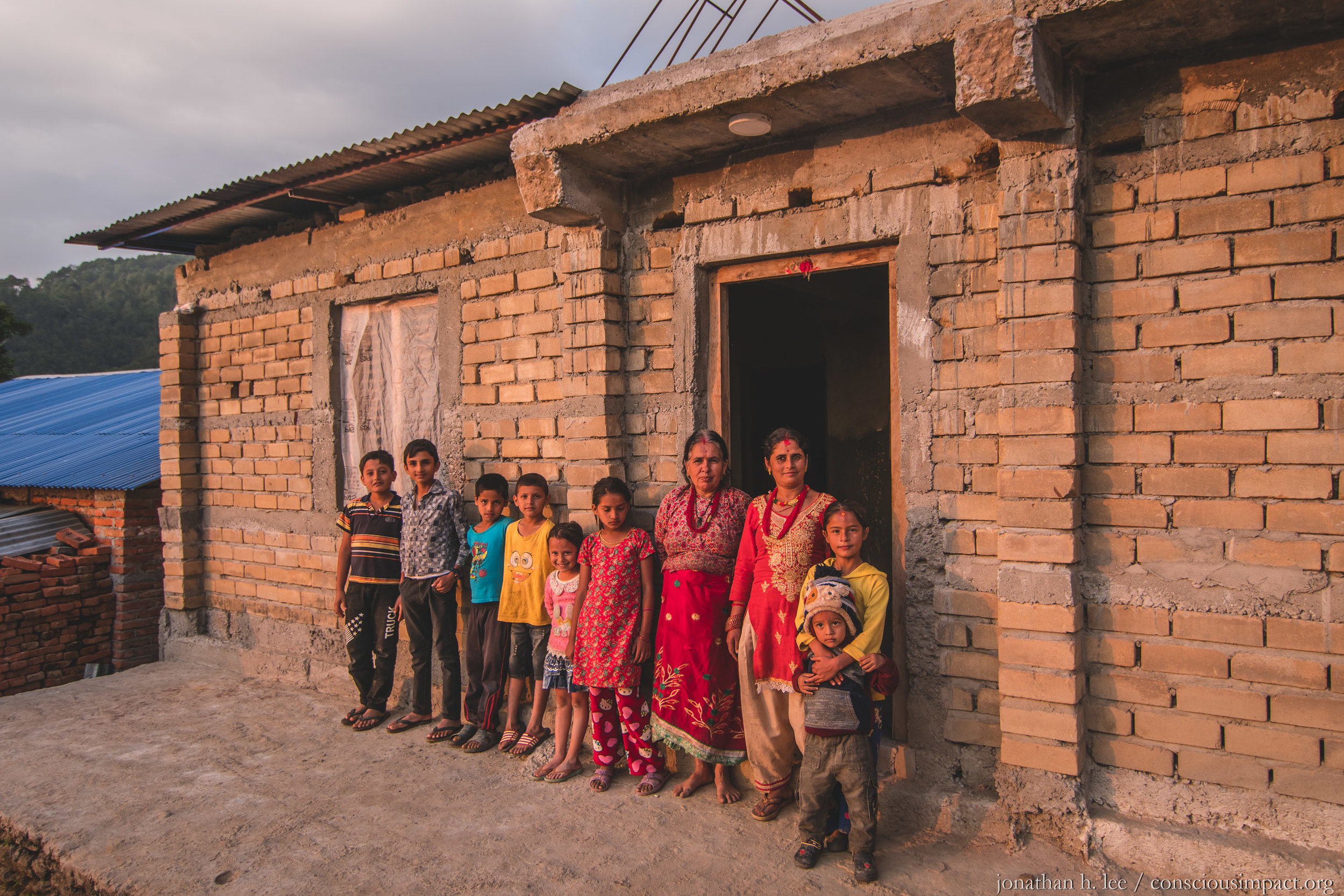 The Dahal Family in Bimire stands in front of their nearly completed 4-bedroom home. Photo by Jonathan H. Lee