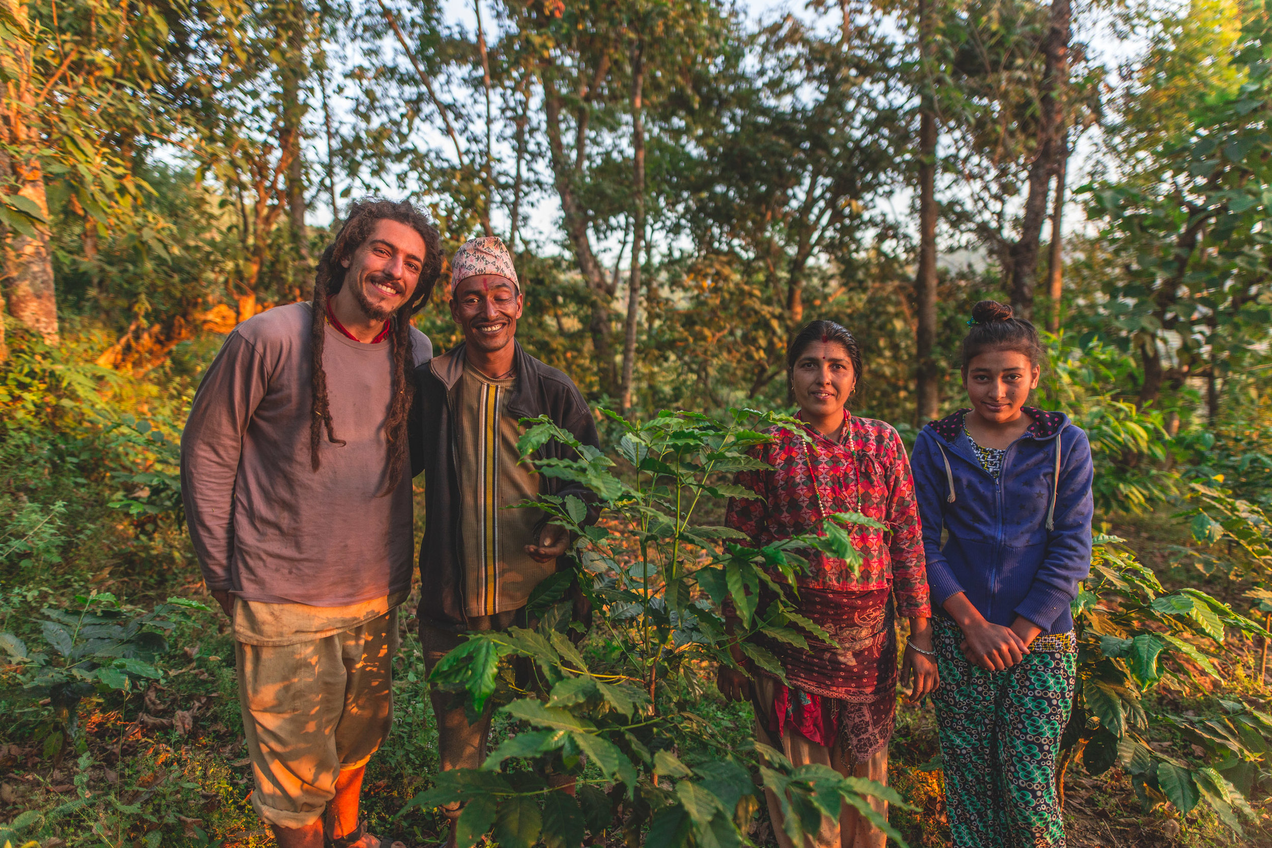 Narayan Bhattarai with his family and Agricultural Program Lead Greg Robinson. Narayan hopes that this 3-year-old coffee tree will give fruit this December! Photo by Jonathan H. Lee