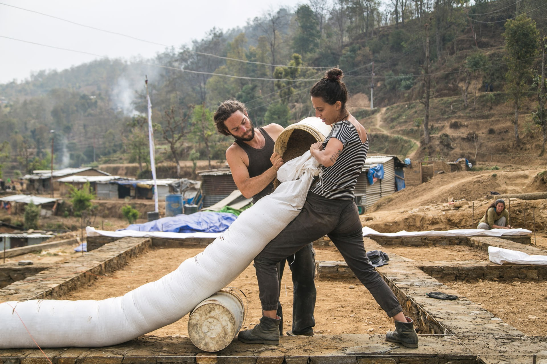 Learning to fill earthbags on site at a 2017 home construction with Conscious Impact. Photo by Jonathan H. Lee