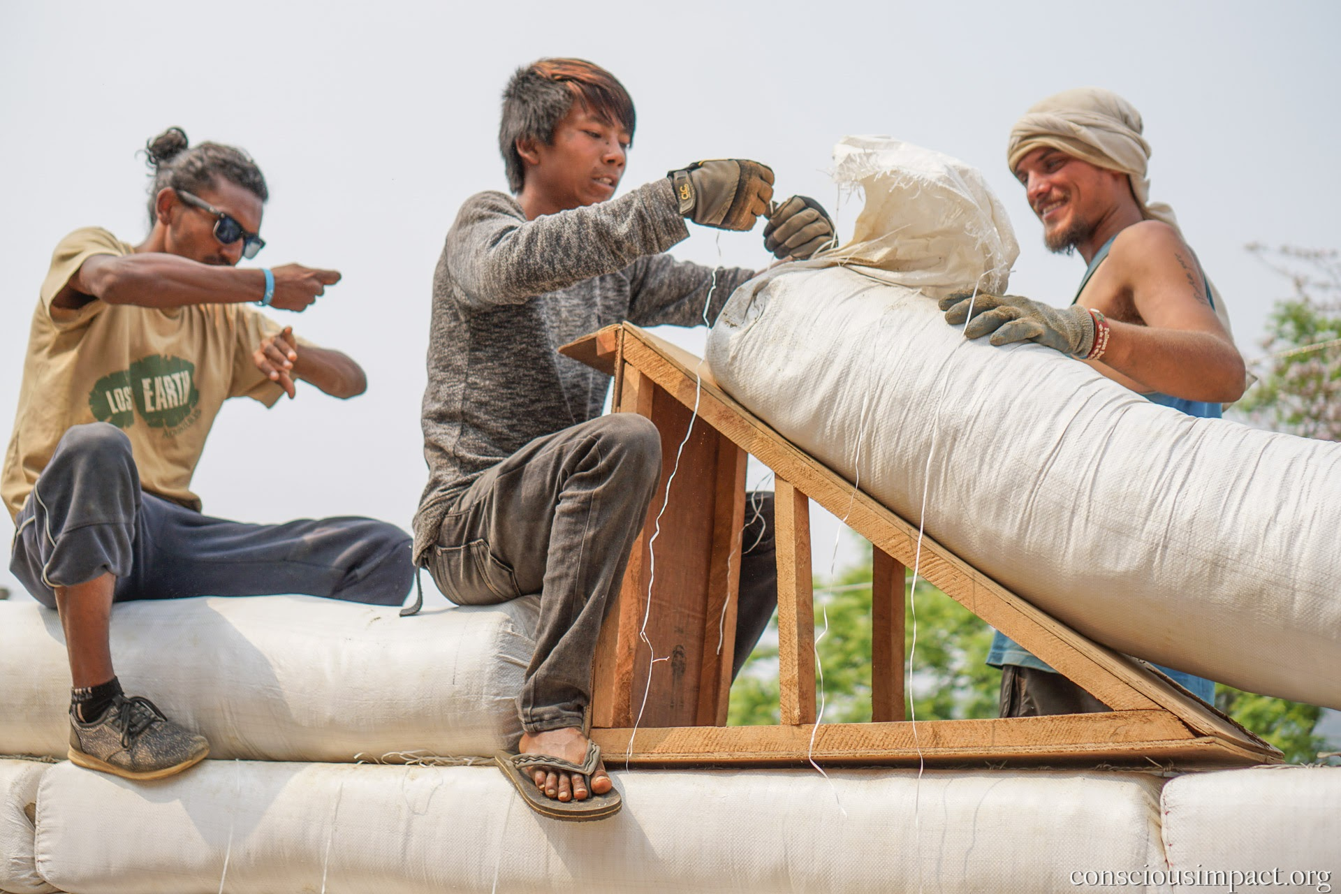 The Conscious Impact construction team, alongside local community members, build a home for a family in need in rural Nepal. Photo by Jonathan H. Lee