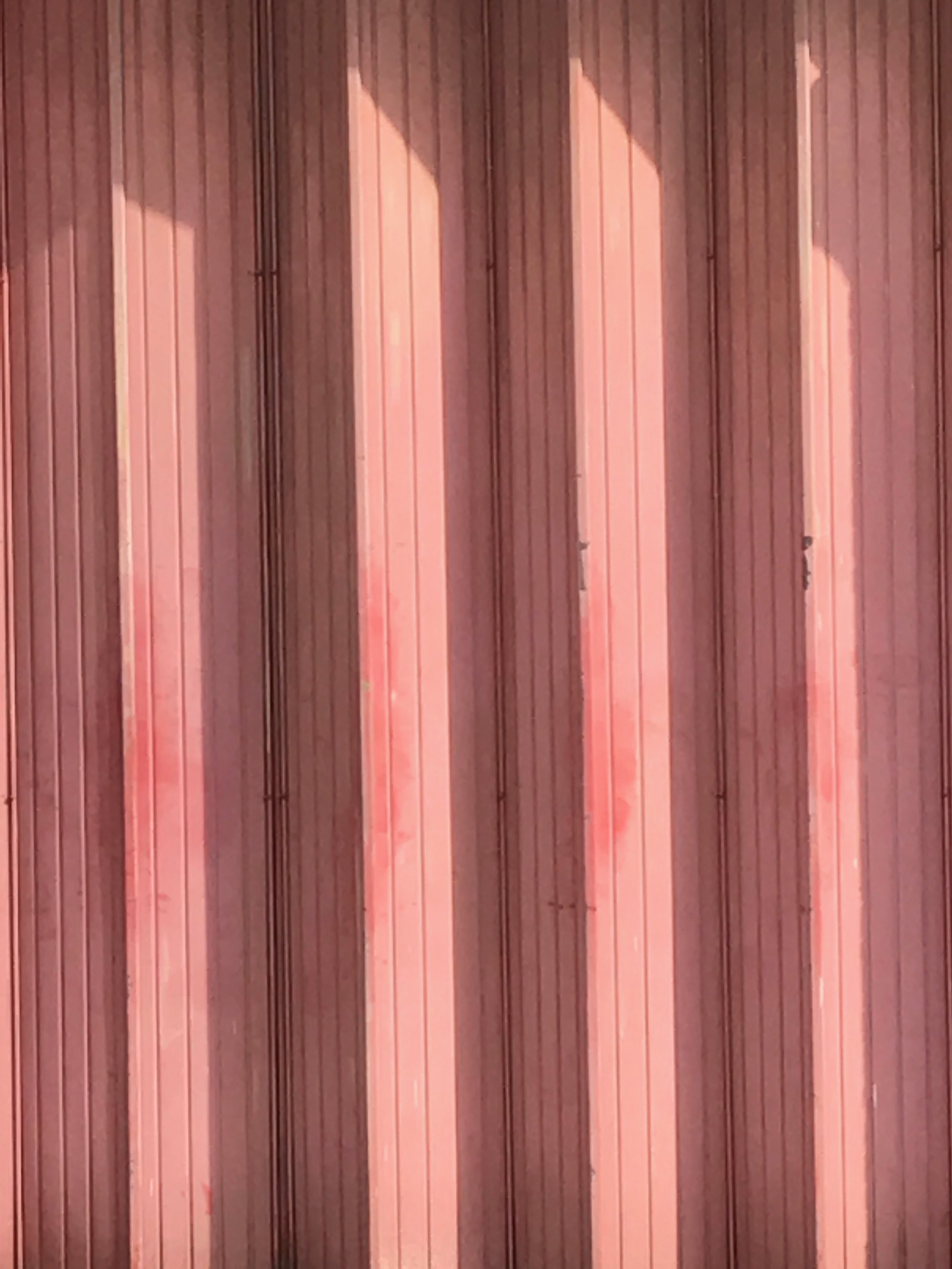 An old garage door on an industrial estate in London with a gorgeous pink terracotta shade as colour inspiration. Image by Camilla Pearl Interiors Blog England.