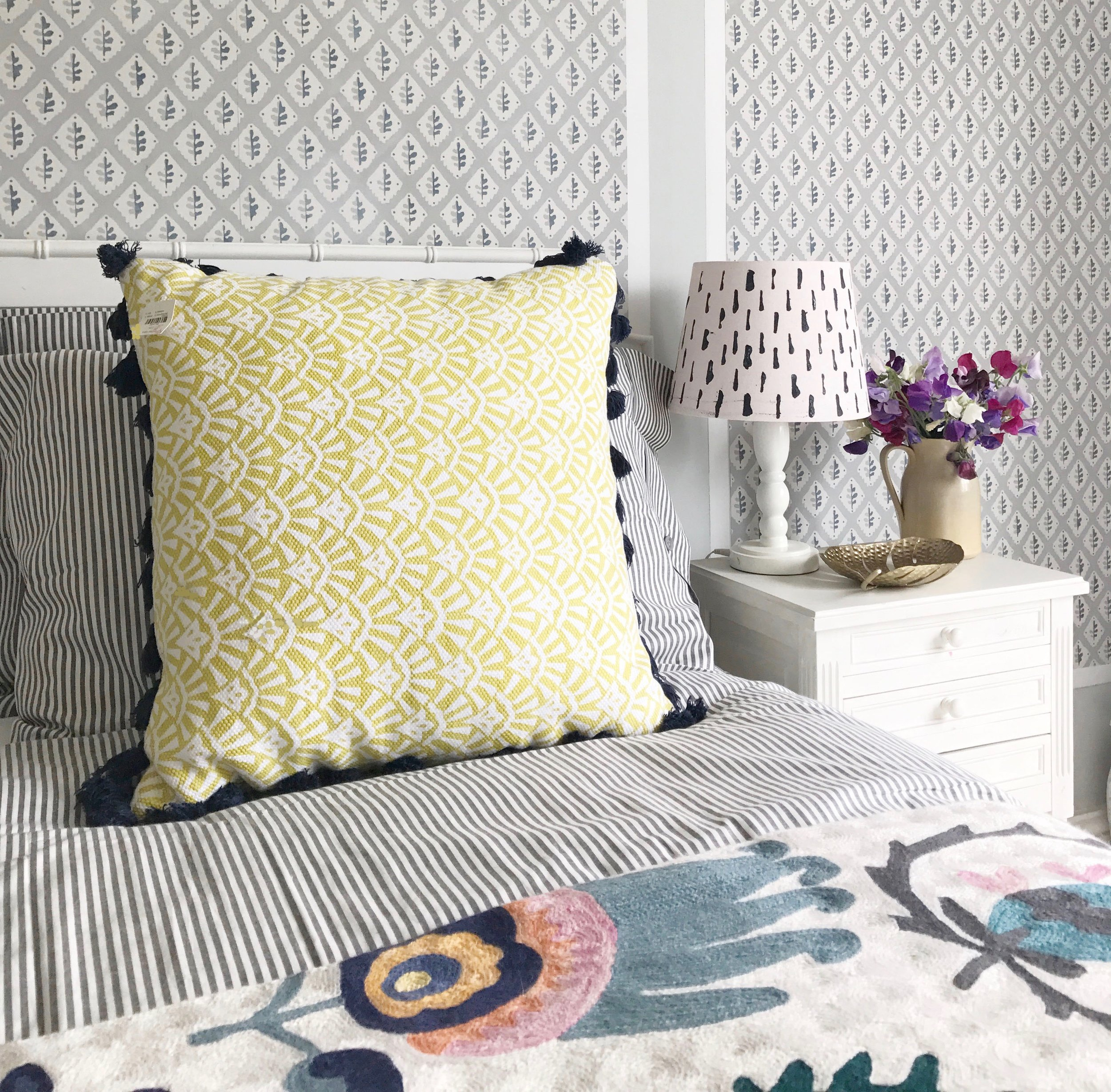 Ideas for adding colour to a light grey bedroom, add in pops of yellow and pink in your accessories with added pattern.
