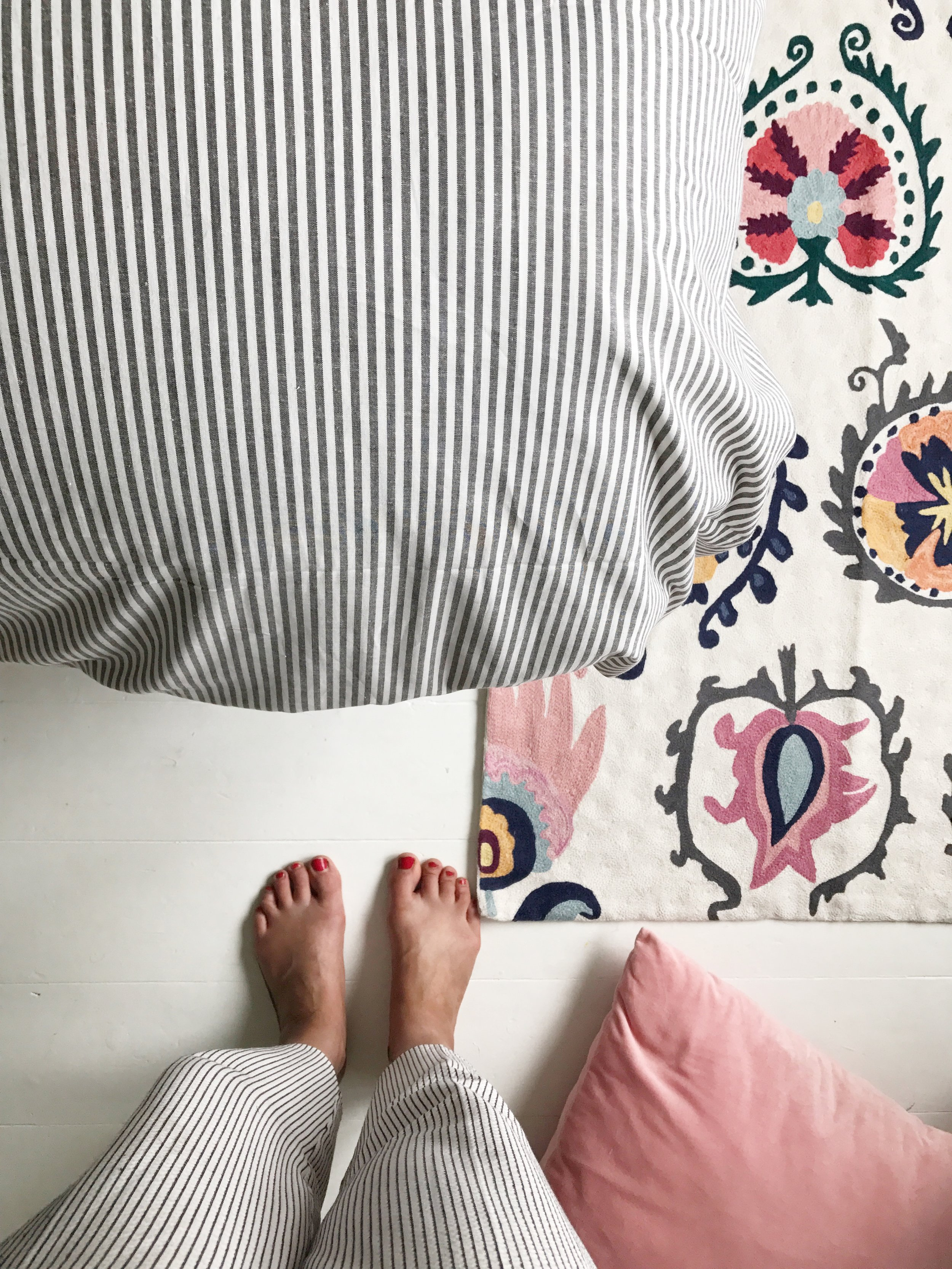 Light grey bedroom decor, adding in pops of zingy yellow and a rug for interest.
