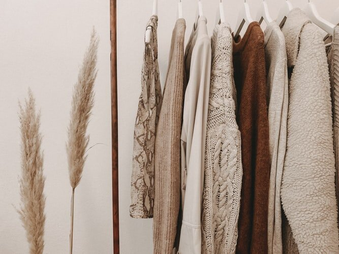 Neutral colored closet wardrobe with various fall and winter sweaters