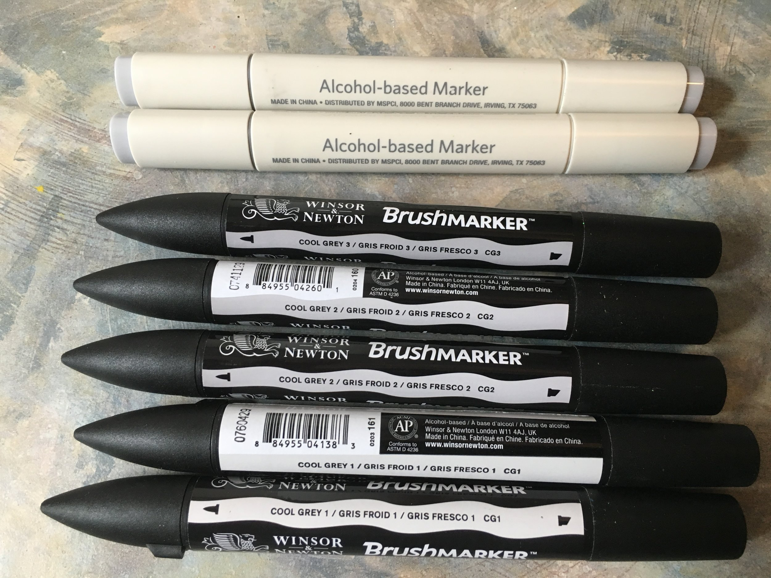 "These are my go to grays. The Windser & Newton Brush Markers are awesome, with consistent tones pen to pen, and excellent, flexible brush nibs for getting good, controlled thick to thin shading and volume into a drawing. Downside, they're not cheap, or refillable, and as I use the cool gray 01 and 02 the most, my burn rate is about a pen every couple weeks. A LOT of artists prefer Copic markers, and if you have the budget or work for a company that'll cover your costs, Copic is definitely the industry standard, at least on the west coast and in Japan. I find them over priced and have little desire to refill anything, so my loss, i guess. A lot of folks also like Prisma-Color, and I have a heap of those for certain colour ranges. For cool gray, though, these have me happy.  The other two are an example of alcohol based markers, which smell more and deliver a deeper, often richer tone. These two are from Artist Loft, so a bit cheaper from Michaels, though similar to Copic inks, they won't bleed or discolour if I add water colours over top of them. i tend to use these and a few alcohol based colours - like my Chartpak AD Marker ""Brick Red"" tat's been my go to for a base rust tone for years - when I want to add some darker tone that compliments the gray scale range with a bit of bolder umph."