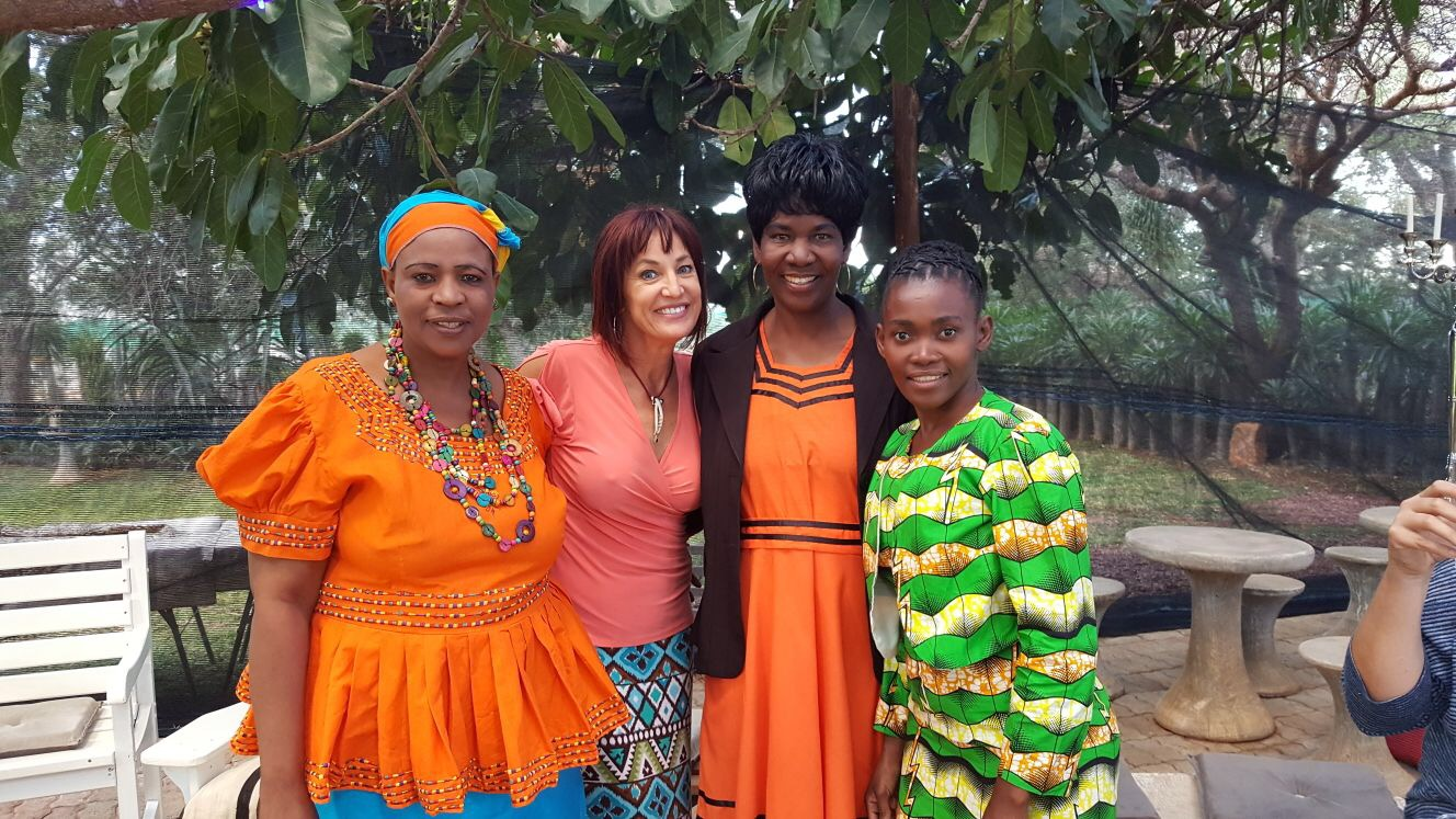 Kiley Doll standing shoulder to shoulder with a few of the women in her female empowerment program in Africa.