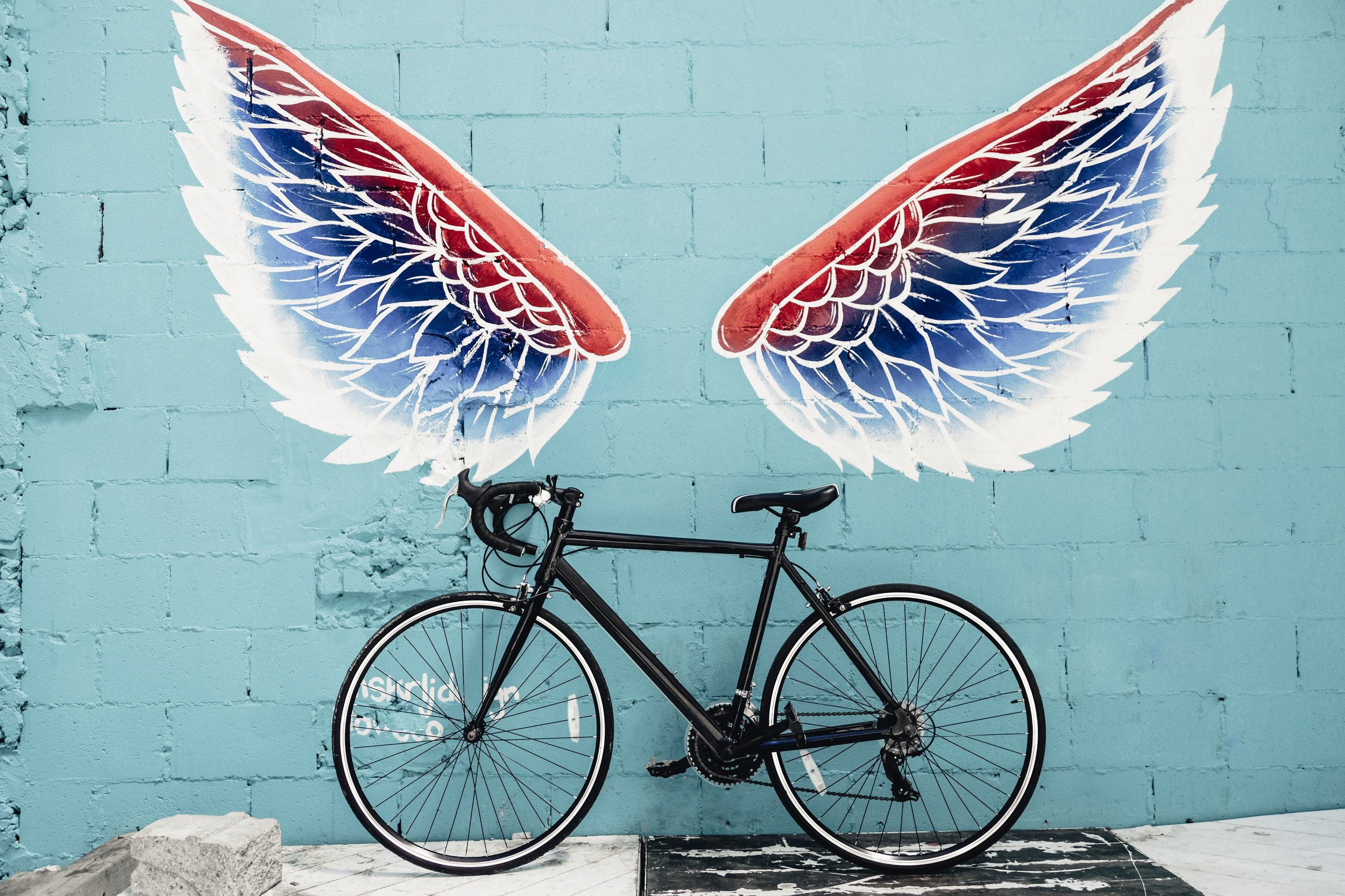Canva_-_Black_Road_Bike_Leaning_on_Red-blue-and-white_Wing_Graffiti_Wall.jpg