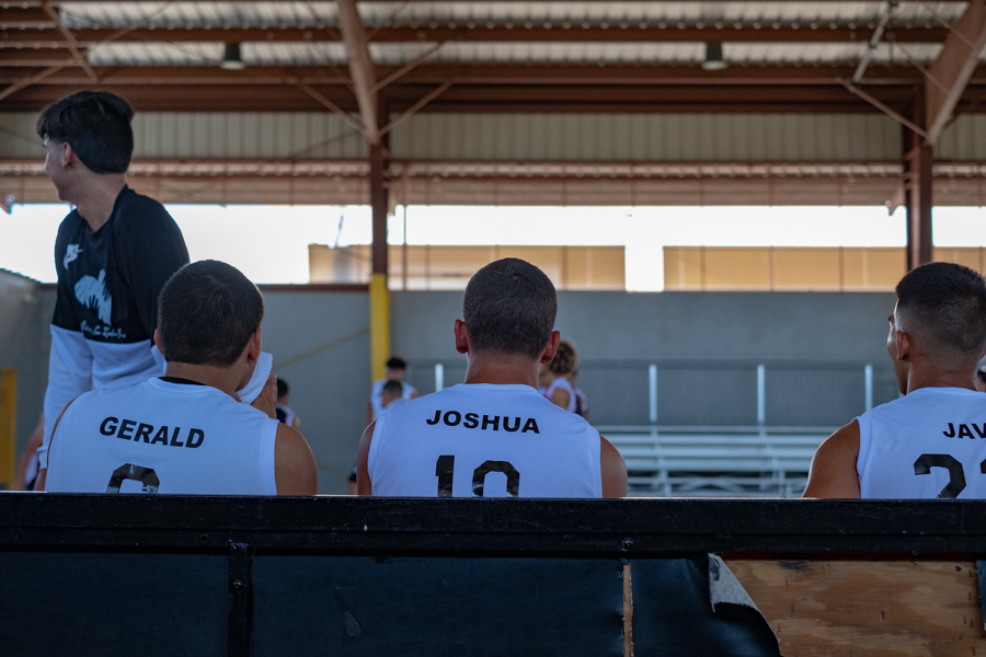 Basketball team watches the action on the court