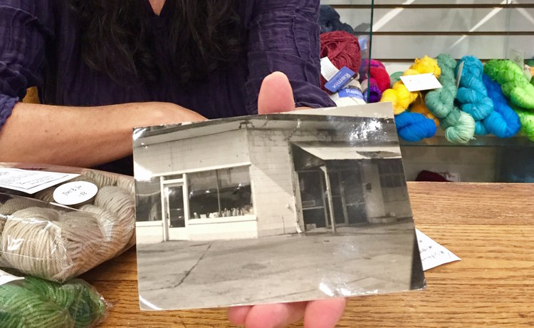 Emily Wexler of Cozy with a photo of the gas station once housed in Cozy's location.