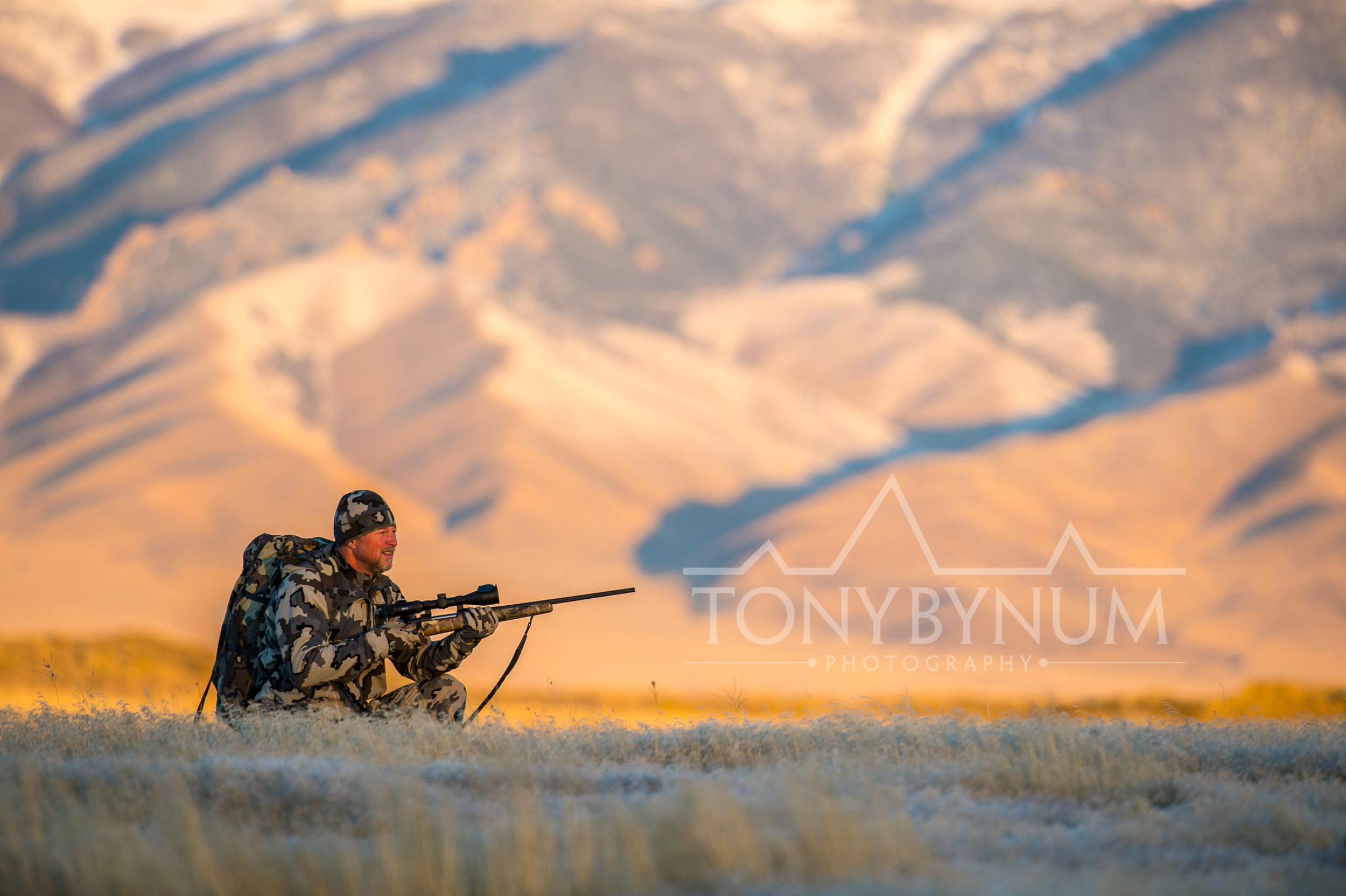 A hunter in Montana holding a rifle in preparation to take a shot. © Tony Bynum