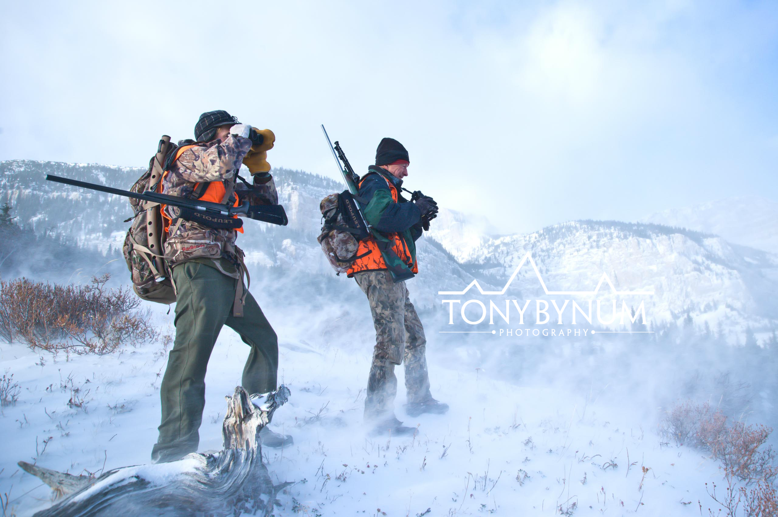 Two mountain hunters one glassing from a wind swept snowy ridge in Montana. © Tony Bynum
