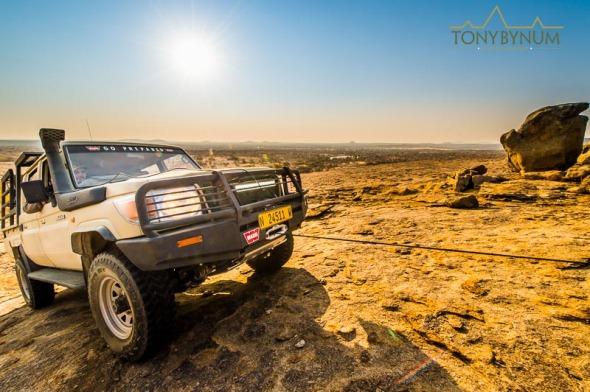 Safari vehicle winching up rock face in Africa