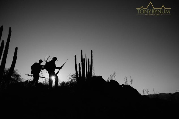 Hunters on a ridge backlit by sun, backpacks hiking