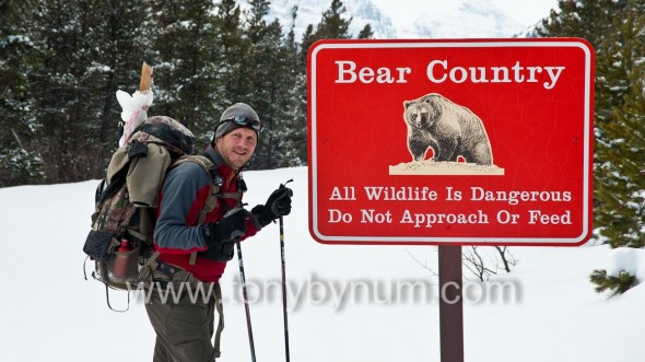male skier packing deer leg on pack in front grizzly bear sign,