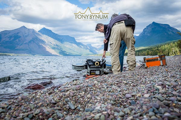 "Brad Ohlund, Director of Photography, filming the ""National Parks Adventure"" movie along the shore of Lake Mcdonald, glacier national park, montana. © Tony Bynum"