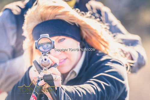 A woman looking though the scope on a hunting rifle. La Pampa, Argentina ©tonybynum.com