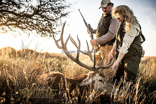 A woman admires her freshly killed trophy red stag on the Los Molles Ranch. La Pampa, Argentina ©tonybynum.com