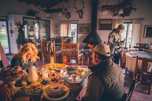 Power is sometimes an issue in La Pampa. Just in case it goes out, there are always candles on had. Candle lit breakfast offers a quanta, more romantic experience. Here a husband and wife sit at the breakfast table together. La Pampa, Argentina ©tonybynum.com