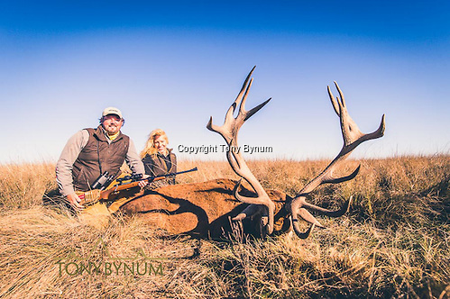 Husband and wife hunter with a trophy, free range, stag from Los Molles ranch. La Pampa, Argentina ©tonybynum.com