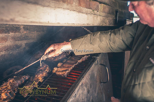 The cook checks the meat for doneness. La Pampa, Argentina ©tonybynum.com