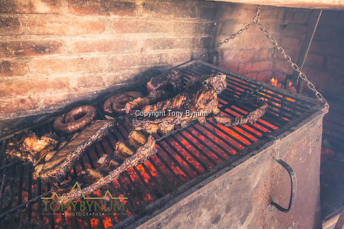 Ribs, sausage, and steaks cooking over an open pit La Pampa, Argentina ©tonybynum.com. The fire is built in the box next to the grill. As the coals become ready, they are shoveled underneath the grill.