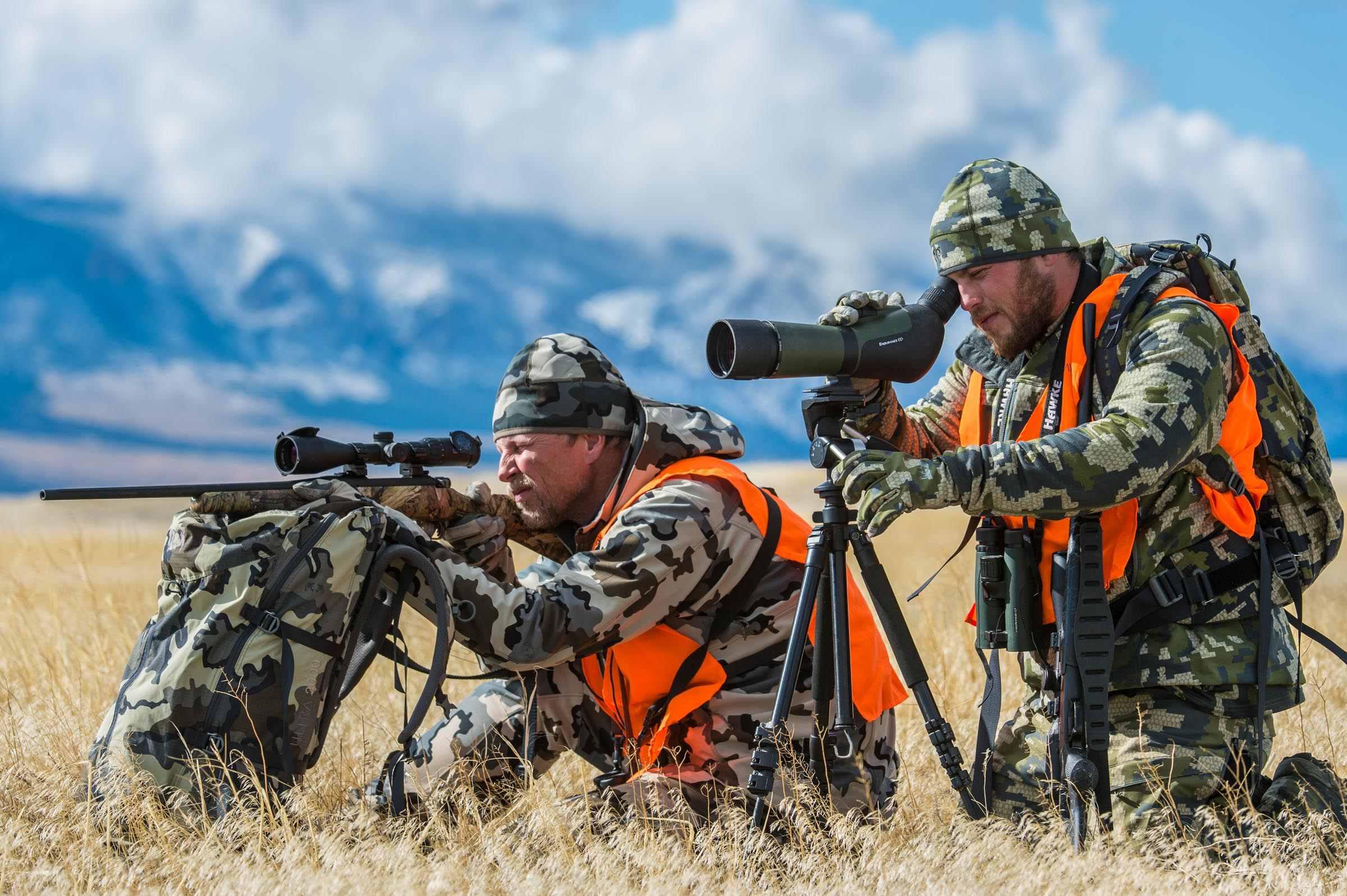 Two hunters one looking through a spotting scope one through a rifle aim to hunt deer on the Montana prairie in the shadow of the Rocky Mountains.  © Tony Bynum