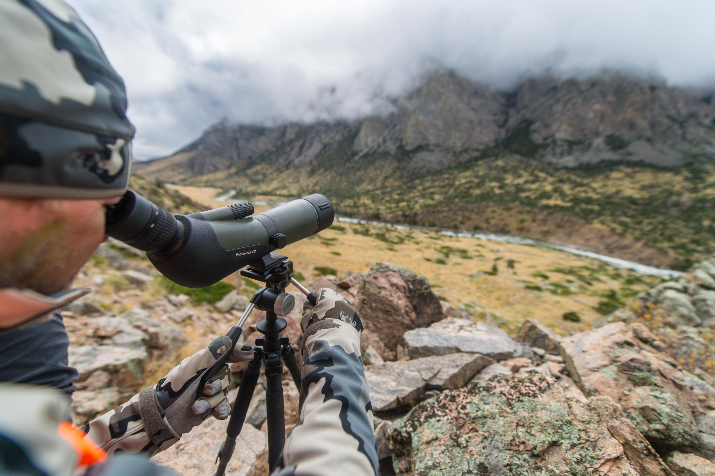A sheep hunter looking for game in the Rocky Mountains looking through a Hawke Spotting scope.  © Tony Bynum