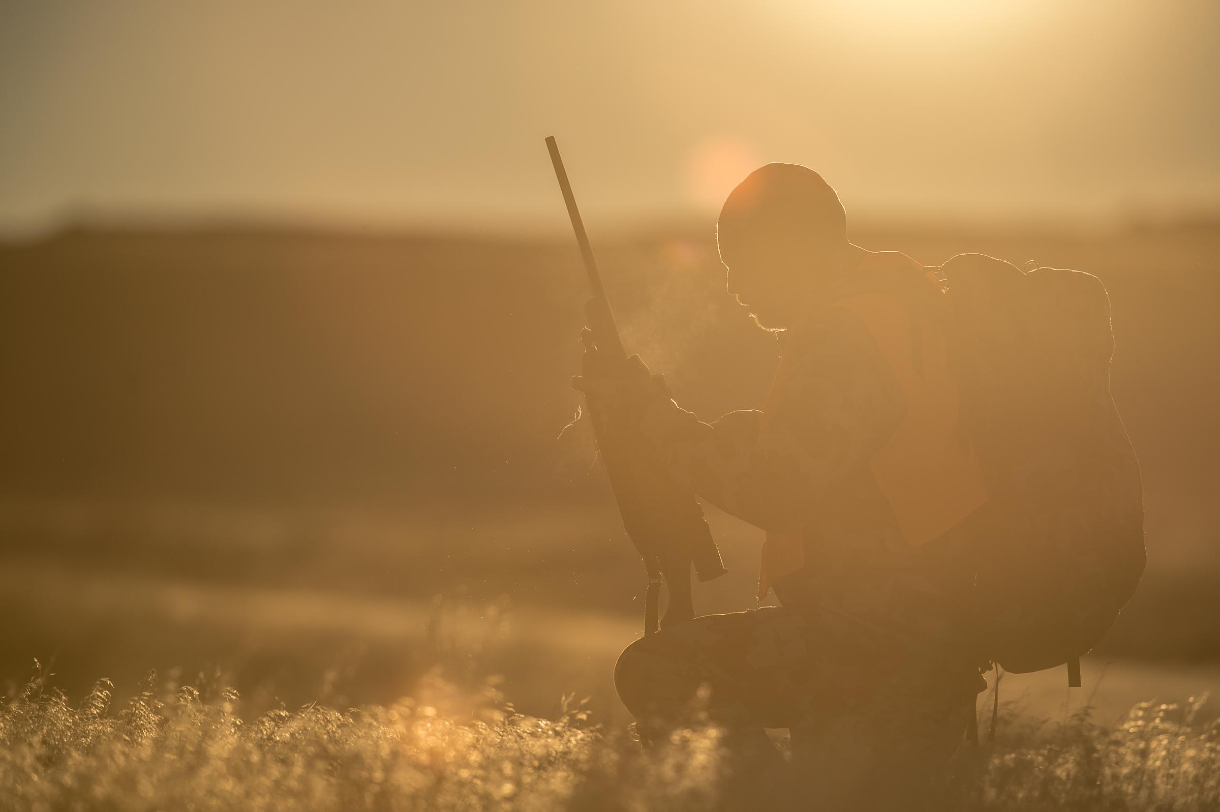 A big game hunter kneels in the early morning light to check his gun before taking a shot.  © Tony Bynum