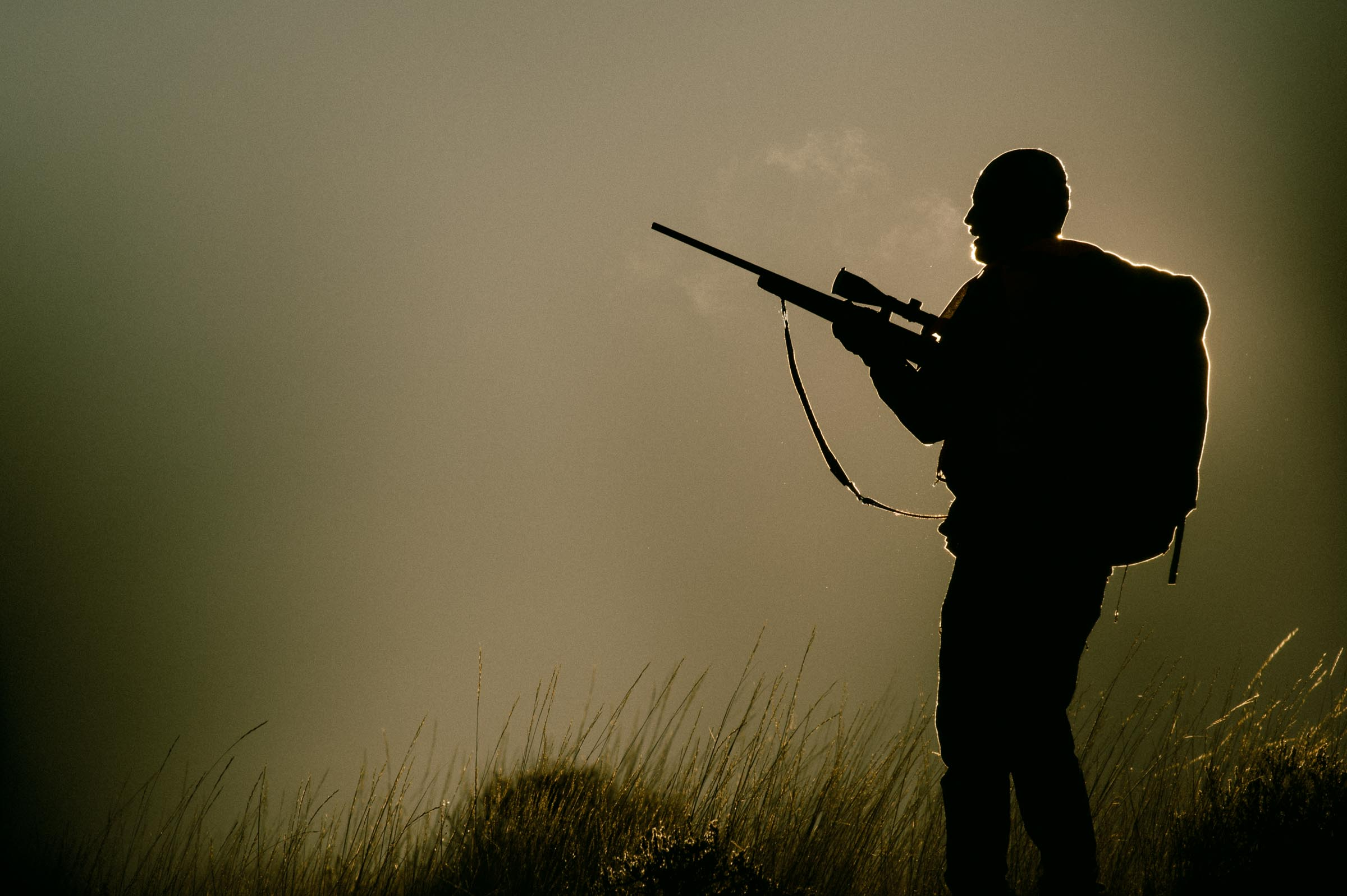 A rifle hunter stands backlit steam emitting from his mouth on a cold morning in Montana. © Tony Bynum