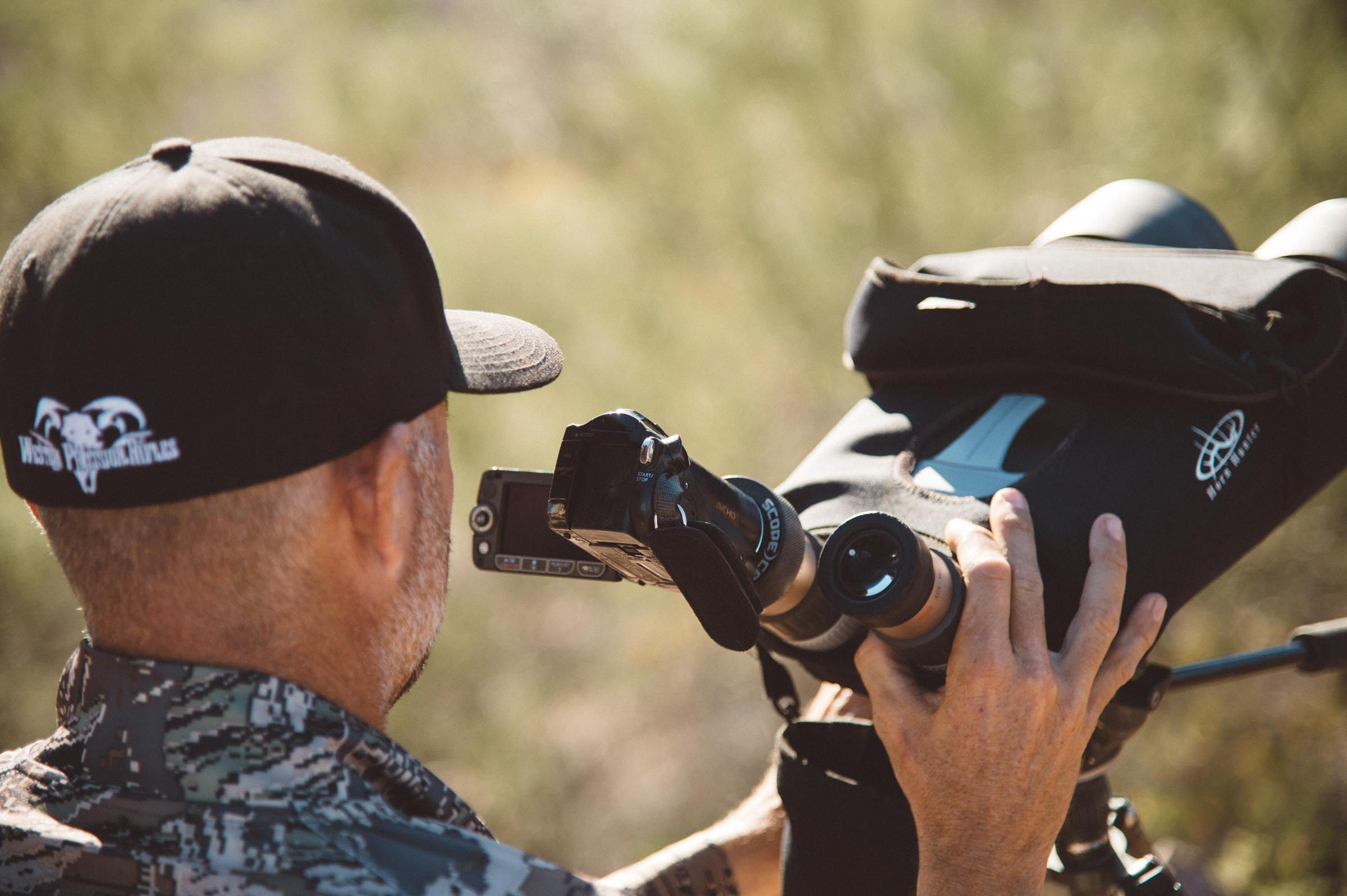 Hunter filming with a digital video camera though a pair of Kowa Optics.  © Tony Bynum